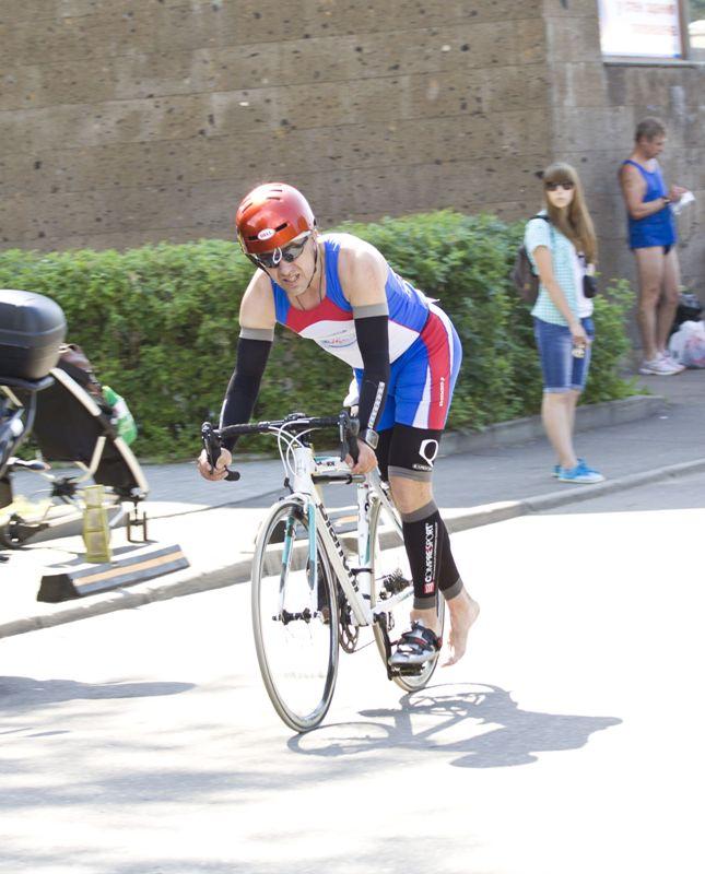 Алексей Соболев, уже на подъезде к транзиту был готов спрыгнуть и побежать к своему месту для переодевания на бег. Кепка, как мы видим, предусморительно уже находится под шлемом.. :)