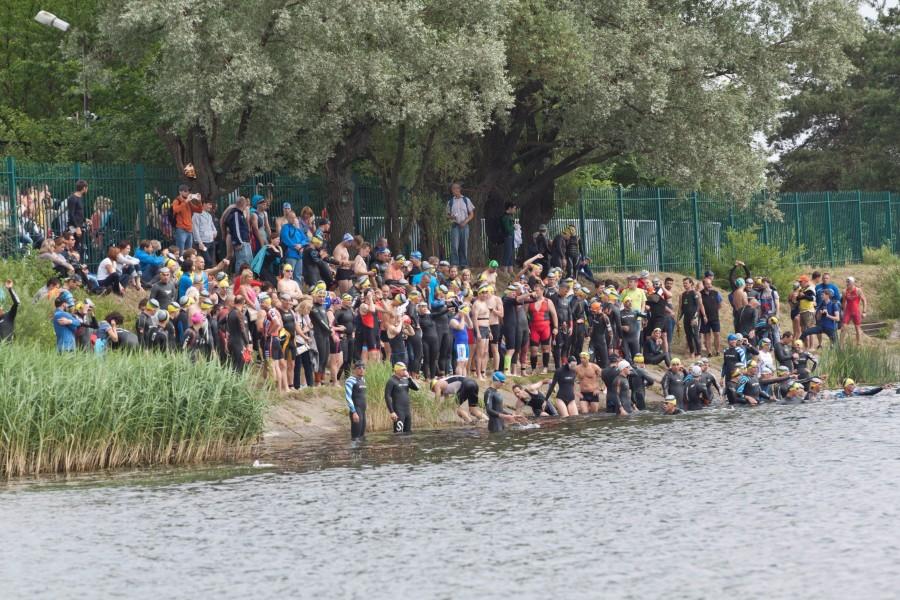 Участники триатлона собрались на другом берегу озера, в предвкушении водного этапа. Еще одно мгновение и старт!